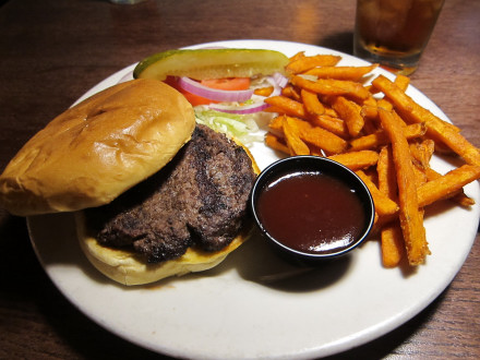 Old fashioned burger with toppings on the side and barbecue sauce added