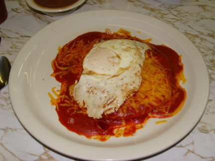 Red enchiladas with an egg on top