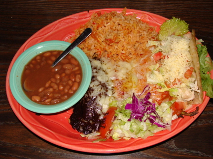 Combination plate with mole enchilada, red enchilada, chile relleno, and chicken taco