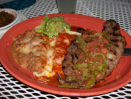 Tampiqueña steak with a red enchilada and guacamole
