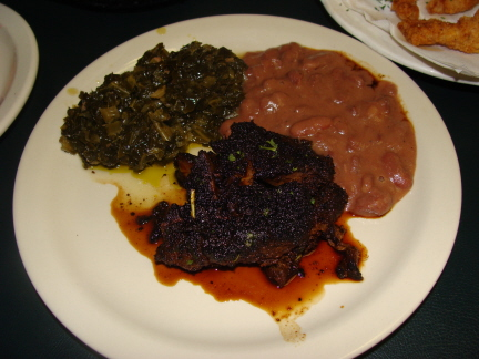 Blackened pork chop, collard greens, and red beans